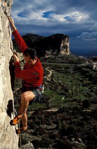 Uomo scala una parete di roccia